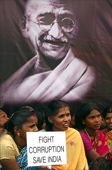 A supporter of Anna Hazare holds a placard in front of a portrait of Mahatma Gandhi.