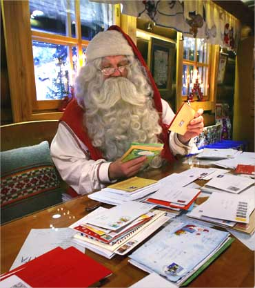 A man dressed as Santa Claus looks over letters received at the Santa Claus Office in Rovaniemi, Finland.