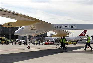 Team members push the solar-powered HB-SIA prototype after it successful landing on the tarmac of Cointrin International airport in Geneva on September 21, 2010.