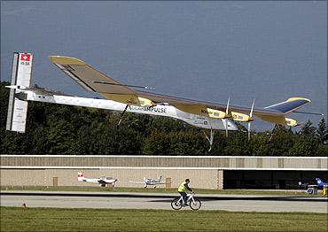 Solar Impulse's CEO and pilot Andre Borschberg is followed by a team member on a bicycle.