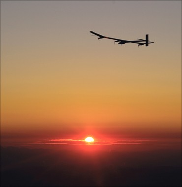 Andre Borschberg flies the solar-powered HB-SIA prototype airplane at sunrise.