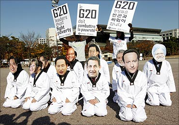 Oxfam protesters wearing masks of G20 leaders urging them to fight poverty in Seoul.