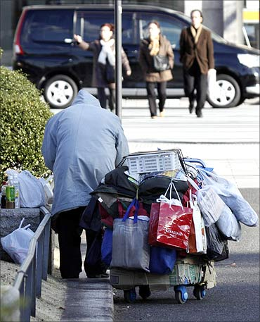 A homeless man packs up his belongings on a street in Tokyo.