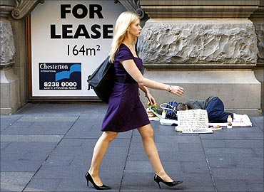 An office worker walks next to a homeless woman in central Sydney.