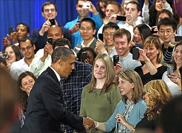 Obama greets attendees as he arrives for a town hall meeting at Facebook headquarters.