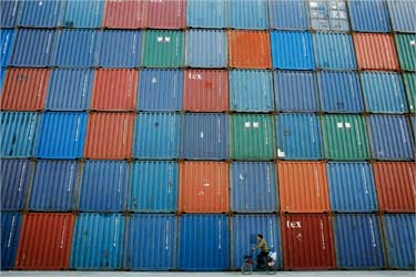 A man rides a bicycle past containers at a port in Shanghai.
