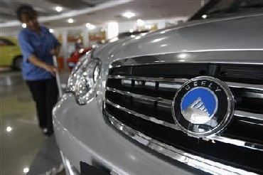 A worker cleans the floor at a showroom in the headquarters of Zhejiang Geely Holding Group in Hangzhou, Zhejiang