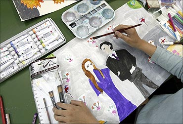 A pupil paints a picture of Britain's Prince William and his fiancee Kate Middleton at a school.