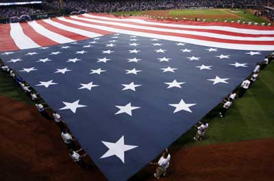 An American flag is unfurled in the outfield before the start of Game 3 of Major League Baseball's ALCS playoff series