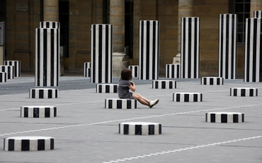 A child sits on a column of 'Les Deux Plateaux' work in Paris.