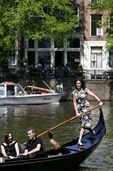 A woman rows her gondola in Amsterdam.