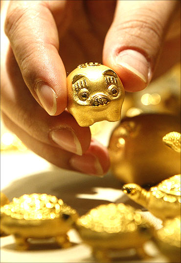 An employee of a jewellery shop holds a gold pig.