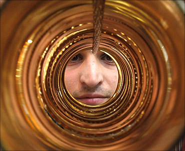 A goldsmith poses with gold bangles in his jewellery shop.