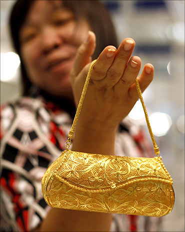 A woman shows a mobile phone purse made of gold.