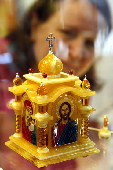 A visitor looks at a chapel, made of gold, silver and amber.