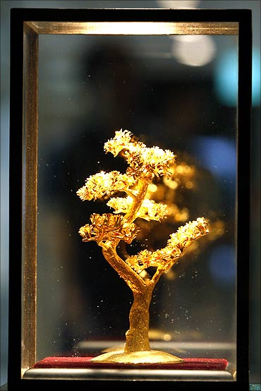 Customers walk past a  gold replica of a pine tree displayed at a jewellery shop