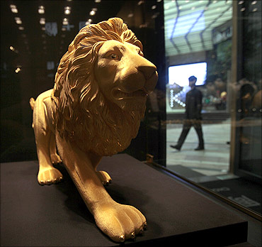 A gold statue of a lion is displayed at a jewellery shop.