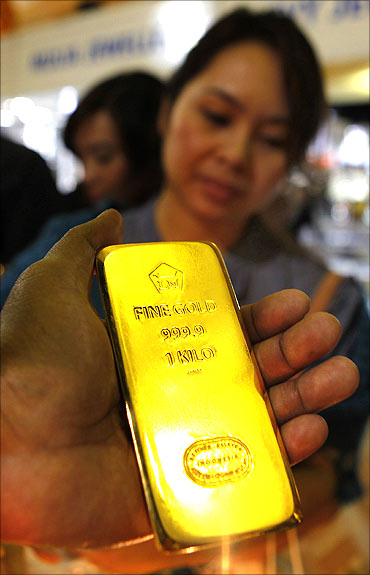 A man shows a gold bar to costumers.