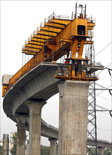 Delhi Metro Rail Corporation (DMRC) employees work at the construction of a flyover in New Delhi.