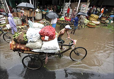 A man transports vegetables through a wholesale market during a downpour in Kolkata.