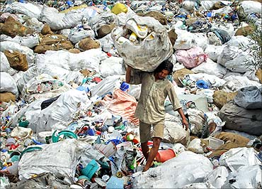 A worker carries a sack filled with used plastic items at a grinding plant near Srinagar.