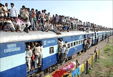 Hindu devotees travel on a crowded passenger train.