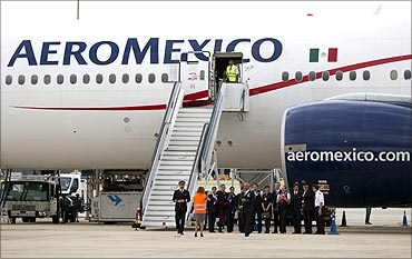 Crew members take photographs near an Aeromexico Boeing 777.