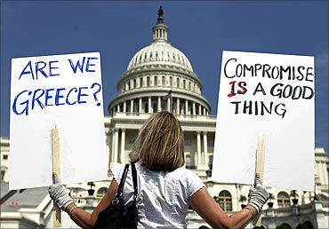 A demonstrator holds placards to protest US debt in front of the Capitol in Washington.