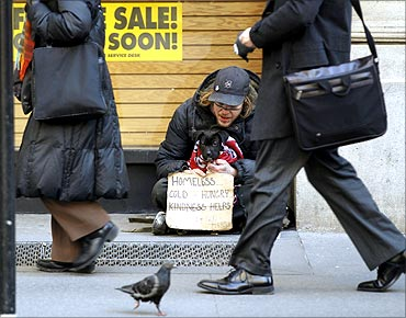 Pedestrians walk past a man as he panhandles for money sitting with a puppy in New York.