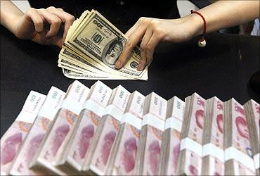 An employee counts US dollars next to yuan banknotes at a bank.