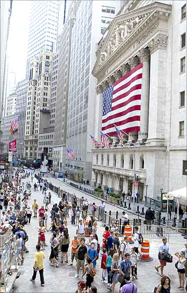 Pedestrians walk on the street in front of the New York Stock Exchange.