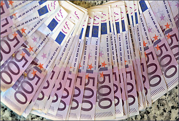 Euro notes are spread out at a bank branch in Madrid.