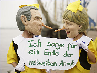 Activists from Oxfam dressed as German Chancellor Angela Merkel and former President George W Bush.