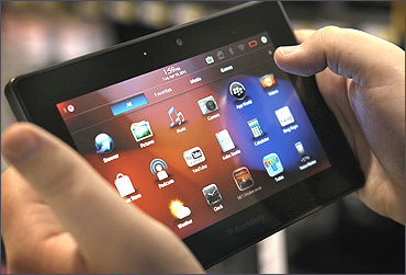 An employee demonstrates a Blackberry Playbook tablet at a Best Buy store.