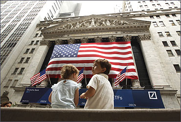 Two children sit on a bench outside the New York Stock Exchange.