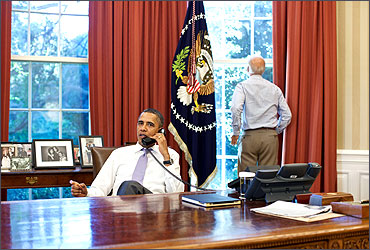 Vice President Joe Biden (R) looks out the window as U.S. President Barack Obama talks on the phone.