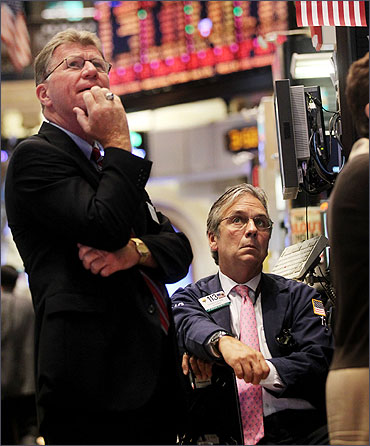 Traders watch a stock ticker on the floor of the New York Stock Exchange.