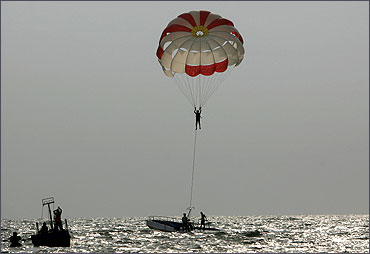 A tourist paraglides on Baga beach in the western Indian state of Goa.