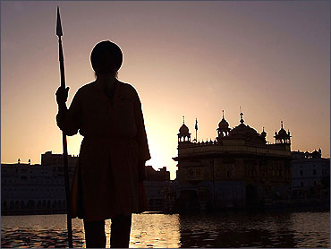 A Sikh temple worker stands guard inside the Golden Temple complex in Amritsar.