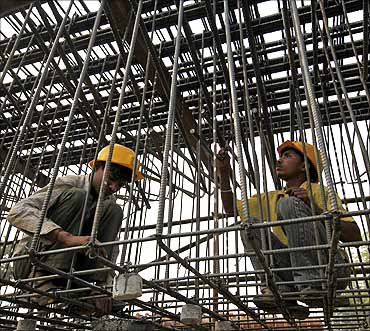 Labourers work at a flyover construction site in Mumbai.