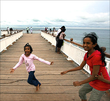Two girls play on a boardwalk at the sea front in Colombo.