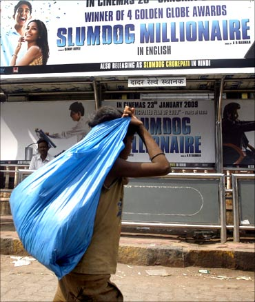 A ragpicker walks past a billboard of the film Slumdog Millionaire at a bus station in Mumbai.