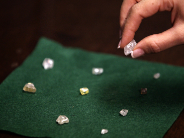 A visitor holds a 17 carat diamond at a Petra Diamonds mine in Cullinan.