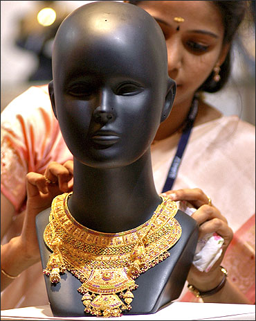 A worker arranges jewellery on a mannequin at a stall in Chennai.