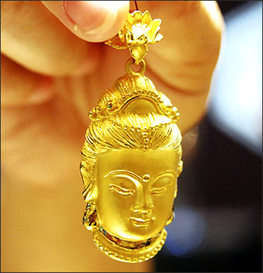 A sales assistant displays a gold accessory in the shape of Buddhist goddess Guanyin.