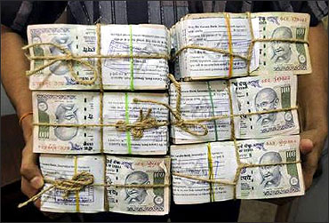 An employee carries bundles of currency notes inside a bank in Agartala.
