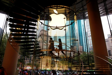 People walk inside an Apple retail store in Shanghai.