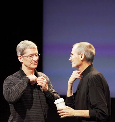 This file photo shows Apple CEO Tim Cook and his predecessor Steve Jobs removing their microphones after a news conference.