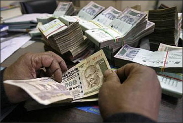 An employee counts rupee notes at a cash counter inside a bank.