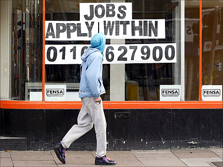 A man walks past a shop advertising job vacancies in Leicester, central England.